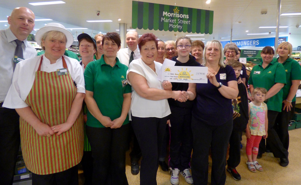 Lynn Bailey recieves a cheque from Linda Felton of Morrisons, watched by Morrisons staff and the BAFF Family Fun Group