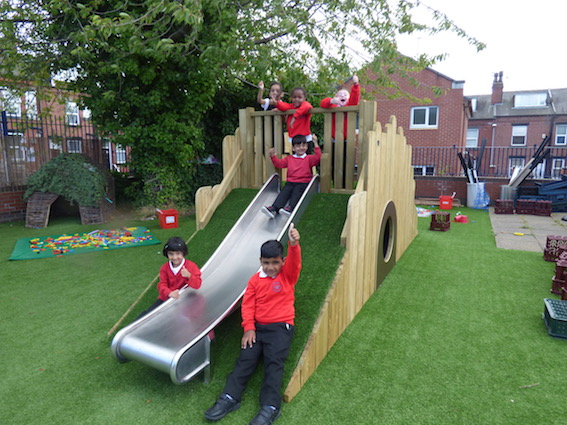 Children give a thumbs up to their new slide