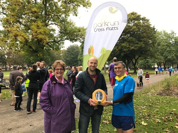 Paul Dewhirst with Mark Hodgkinson and Cllr Angela Gabriel who allocated MICE money to Cross Flatts parkrun to purchase the new flag pictured